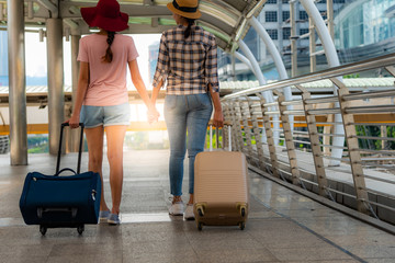 The back of two teenage girls who are friends, walking in the street or the walkway, holding carrying a suitcase, trolley wheel. To summer and travel concept.