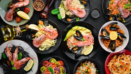 A set of seafood dishes on a black background. Pasta, bulgur, rice, couscous. Top view. Free space for your text.