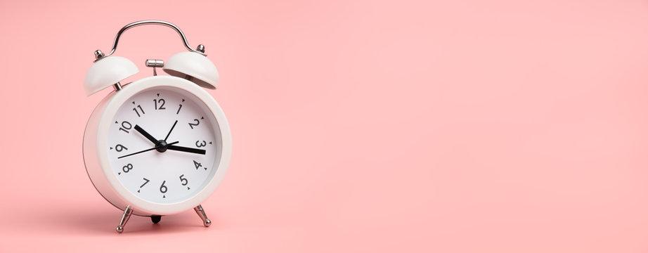 White alarm clock on pastel pink background.