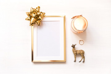 Golden frame with gold bow isolated on white background. Winter minimalistic christmas flat lay.