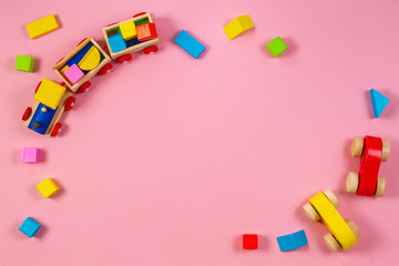 Toys background frame. Wooden toy train and cars with colorful blocks on pink background