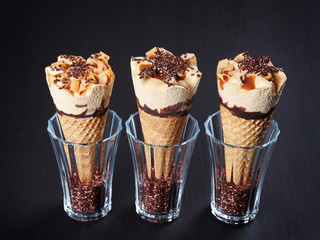 Three caramel ice cream cones, set in glasses filled with sugar crystals, on dark brown background