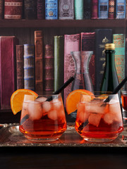 Two glasses of Aperol Spritz, an aperitif cocktail consisting of prosecco, Aperol and soda water, with ice cubes and orange slices