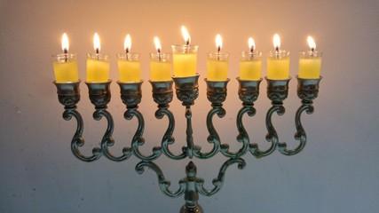 Vintage oil chanukiah - traditional Jewish candelabrum with nine candles burning during the holiday of Chanukah. Hanukkah, Hanukah concept image.