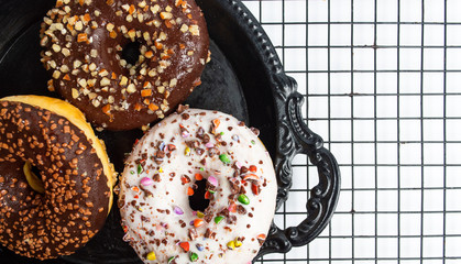 Decorated chocolate donuts on a baking grid