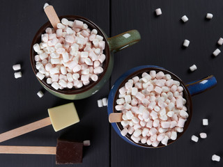 Two cups with hot chocolate and mini marshmallows, one cup being blue and the other one green, with white and dark chocolate cubes, on dark brown background