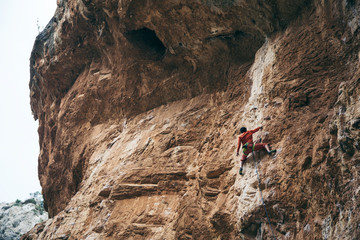 man climbs an overhanging rock, hard route 7c, lead.