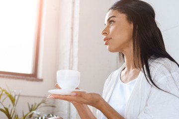 side view of beautiful mixed race girl in white robe holding cup of coffee in morning in bedroom with sunlight