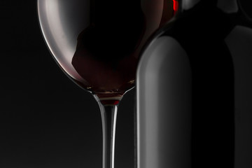 Red wine bottle and glass on the black background