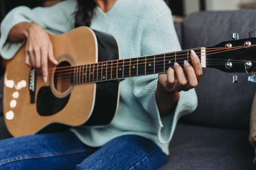 cropped image of mixed race girl in turquoise sweater playing acoustic guitar on sofa at home