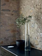 Olivenzweig in Glas Vase mit gefrästem Muster und Holz Schale und Silberschale auf Regal vor Steinwand