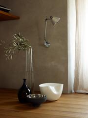 Olivenzweig in Glas Vase mit gefrästem Muster und Silber Schale und Porzellan Schale vor Wand mit Wandlampe und Fenster
