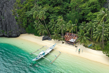 Aerial drone view of turquoise coastal waters and limestone cliffs in El Nido archipelago tourist destination. El Nido, Palawan, Philippines.