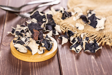 Lot of slices of dry black mushroom jew ear variety on round bamboo plate on brown wood