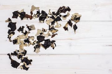 Lot of slices of dry black mushroom jew ear variety left upper corner flatlay on white wood