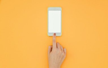 Woman's hand unlocks a smartphone with a finger on the orange background. Copyspace Flatlay