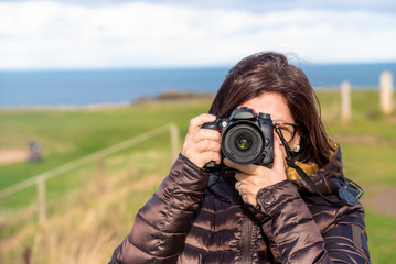 Portrait of Woman Photographer Taking Pictures Outdoor with a Digital Camera on a Sunny Autumn Day