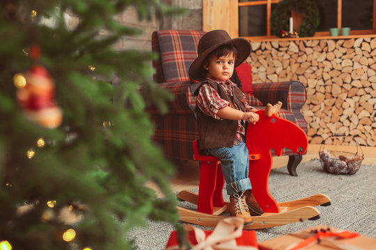 small boy with dark hair, wearing checked red shirt and suede brown vest, hat, is sitting on the wooden rocking moose, checked armchair, Christmas tree, scandinavian interior