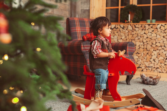 small boy with dark messy hair, wearing checked red shirt and suede brown vest is sitting on the wooden rocking moose, checked armchair, scandinavian interior