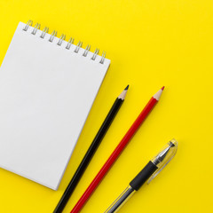 Notebook, black and red pencils, pen on the yellow background. Workspace concept. Flat lay, top view, copy space, mock up, square layout design