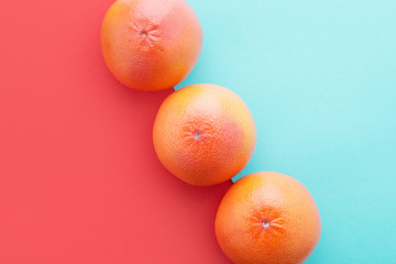 Grapefruits on Living Coral & pastel blue color diagonal background Minimal summer.