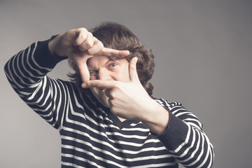 Young handsome man focusing with fingers, framing with hands isolated on grey background. Close up portrait