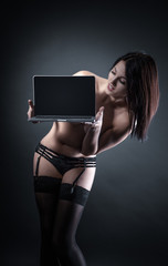 Sexy young brunette woman in black sensual lingerie using laptop and posing on black background wall in studio.