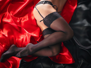 Sexy young brunette woman in black sensual lingerie and in stockings using laptop on red bed in studio.