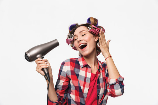 Cheerful housewife with curlers in hair standing