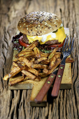 homemade cheeseburger and French fries on rustic wooden background