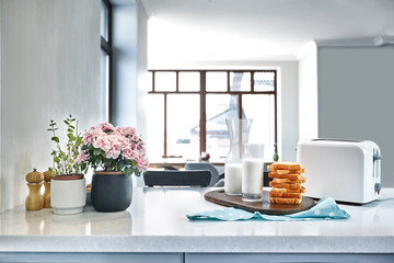 A glass of milk and toast on a table, kitchen background.