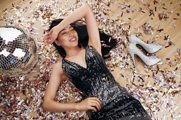 Tired but happy young Vietnamese woman lying on room floor covered by confetti