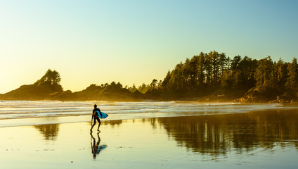 Ein Surfer geht an einem Strand auf Vancouver Island entlang