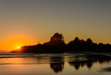 Die Sonne verschwindet hinter den Felsen an einem Strand auf Vancouver Island