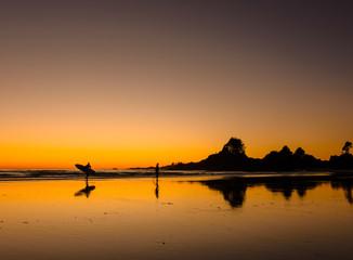 Ein Surfer während des Sonnenuntergangs an einem Strand auf Vancouver Island