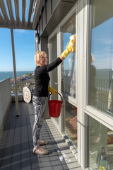 Woman cleaning outside of glass windows using a sponge and a red bucket