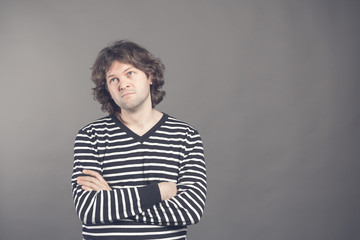 Portrait of caucasian man with bored fed up expression, looks displeased up, being tired to explain his wife where he was at night. Shaggy guy in stripes shirt tired and bored to listen to bullshit