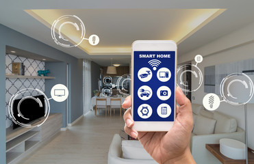 Hand holding smart phone showing the smart home control screen and icon over the Luxury Interior living room with kitchen, service apartment with augmented reality concept