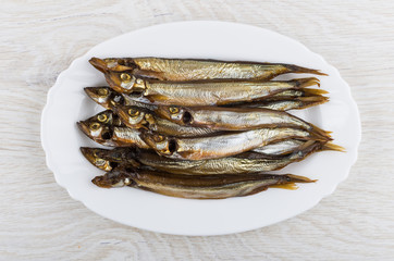 Smoked capelin with heads in oval dish on wooden table