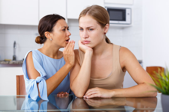 Upset young women friends whispers in the ear  and talking at table in home