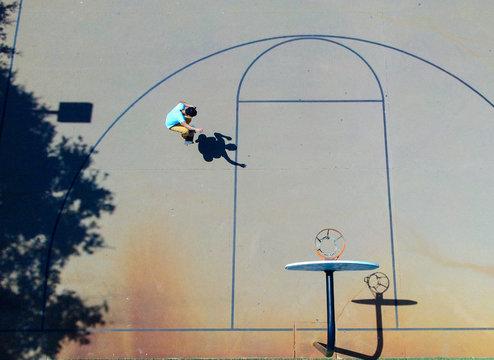 A skateboarder doing an ollie on a basketball court