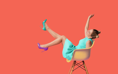 Fashionable woman wearing trendy high heels shoes on coral colored background