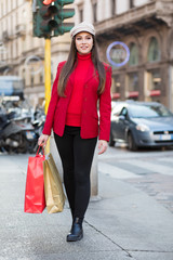 Young woman with shopping bags and Christmas gift in Milan, Italy