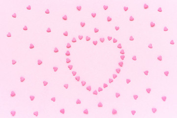 Pink confectionery sprinkles in heart shape on pastel pink background. Concept Valentine's card. Top view Copy space for text