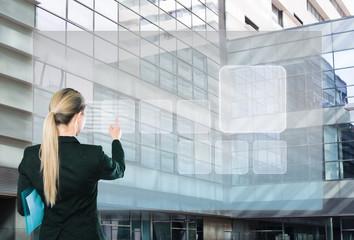 Businesswoman pressing virtual touchscreen