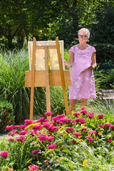 Senior woman painting in garden on sunny day.