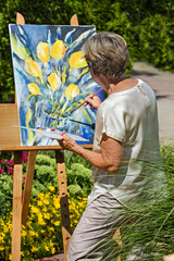 Senior woman painting on easel in garden.