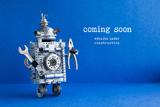 Web site under construction Coming Soon page. Toy robot with hand wrench and pliers. Blue background.