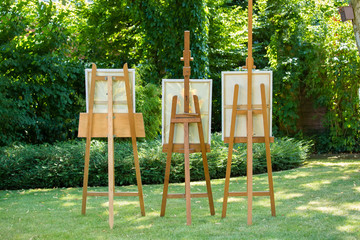 Three wooden easels with paintings.