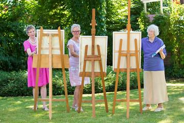 Three senior women painting on canvas in garden.